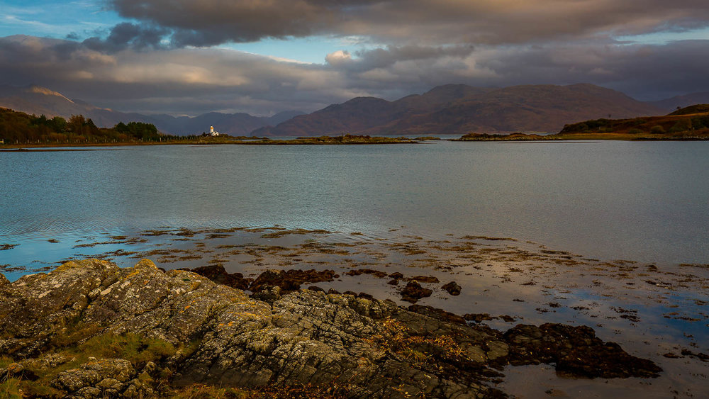 Isle Ornsay Lighthouse and the hills surrounding Loch Hourn.