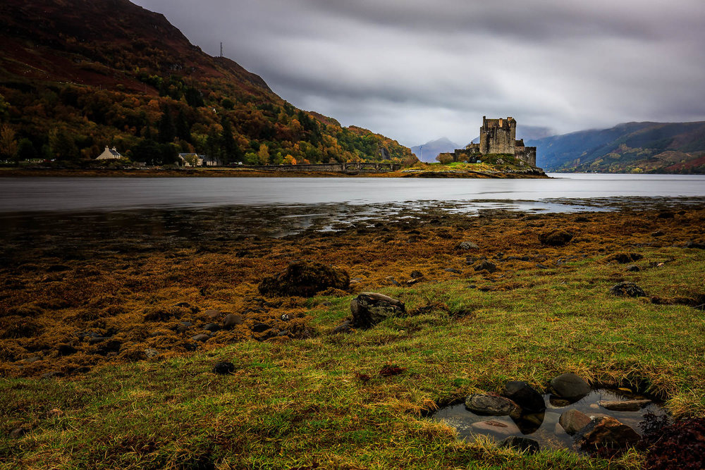 Eilean Donan Castle with autumnal colours and mist shrouded hills of Lochalsh.