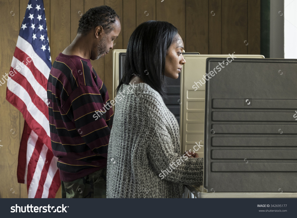 stock-photo-young-black-woman-and-older-black-male-voting-in-a-booth-342695177.jpg