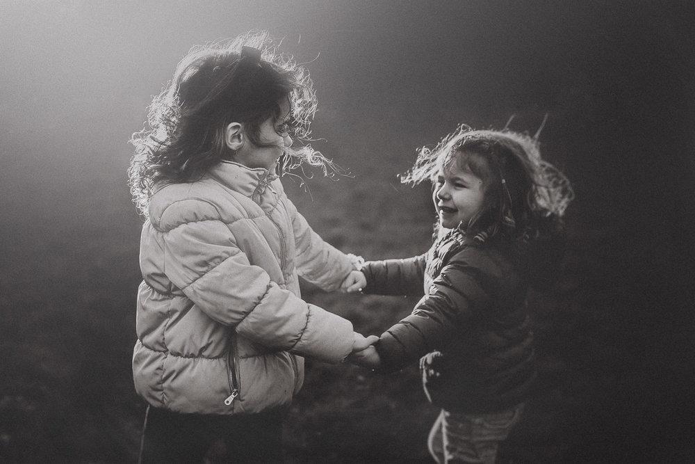 two girls holding hands natural light sunset