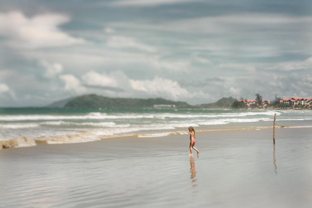a girl walking on a beach in Sabah Malaysia