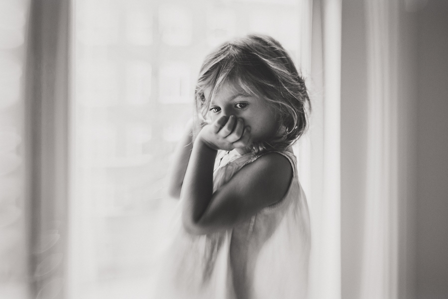 girl looking down by the window in black and white by anita perminova amsterdam portrait photographer