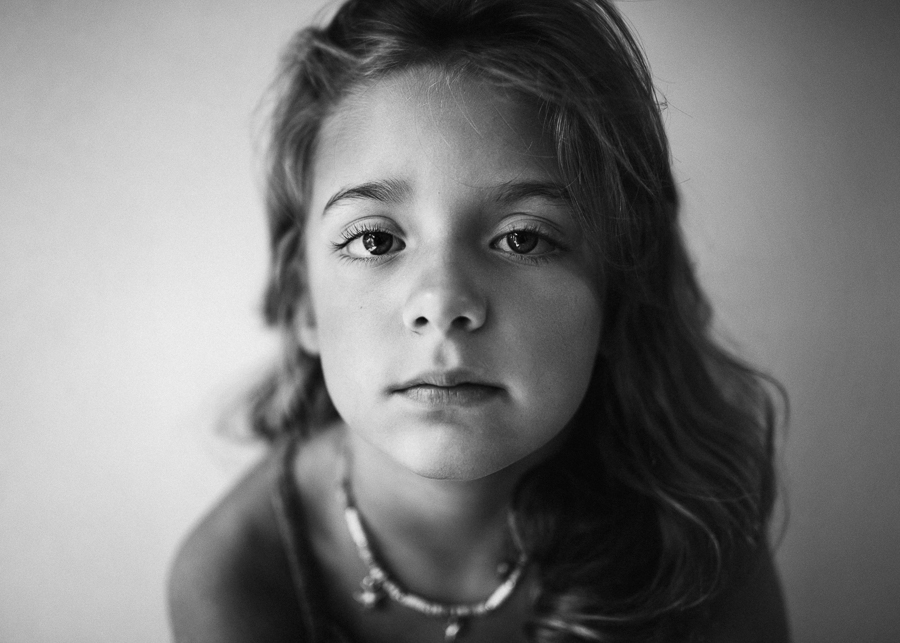 a portrait of a child in black and white looking directly in camera with window side light by anita perminova amsterdam portrait photographer