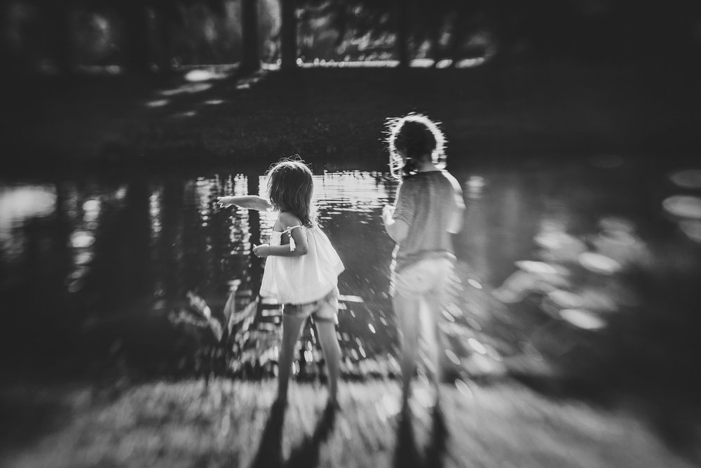 anita perminova amsterdam portrait photographer and filmmaker two girls feeding ducks at beatrix park lensbaby seeinanewway black and white
