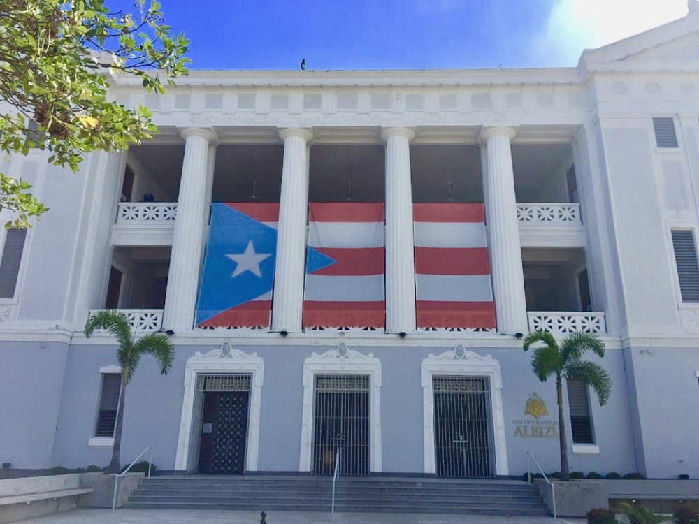The Puerto Rican flag displayed on a university building off a plaza in Old San Juan.