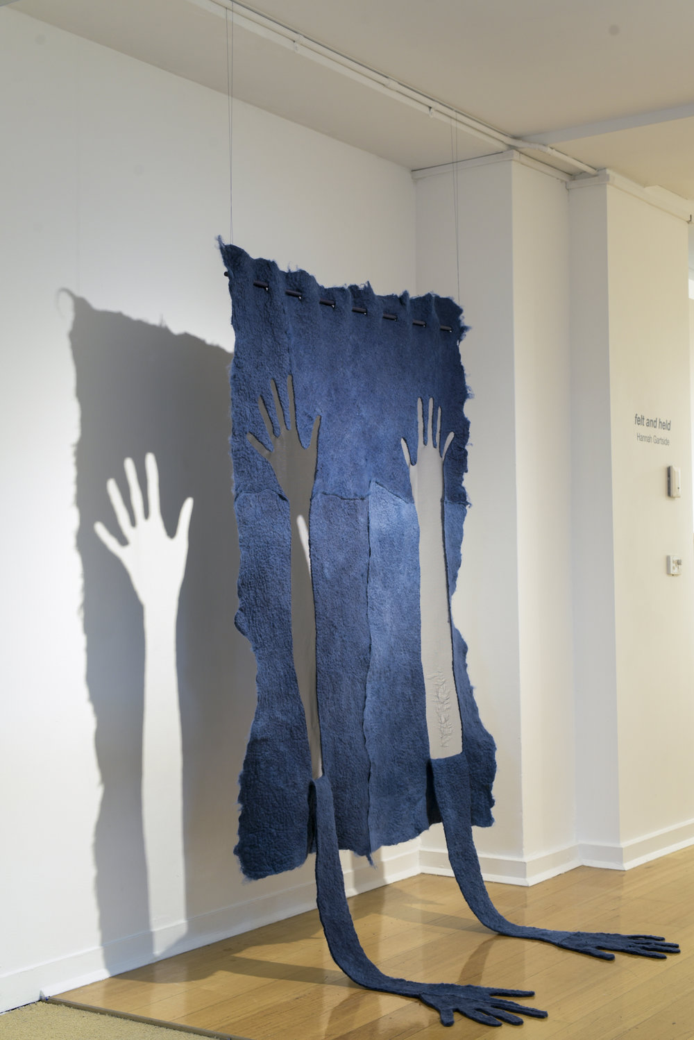 Exultation/ Desperation,  2016, indigo-dyed wet-felted sheep's fleece, found fly net, thread, dowel. H 180cm x w 120cm x D 60cm