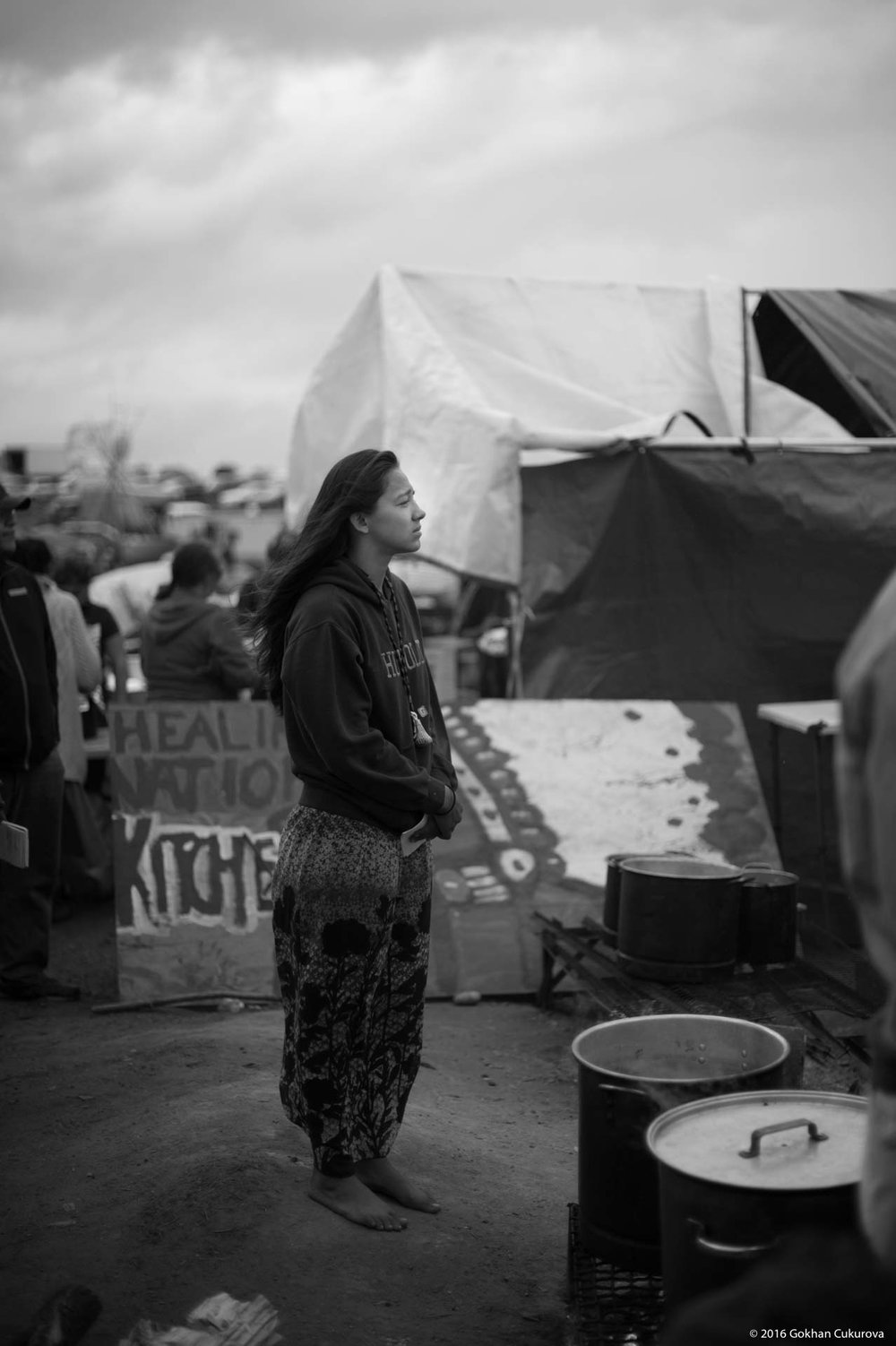 A girl standing under the rain barefoot, listening the Sitting Bull's song sang by the crowd of hundreds.