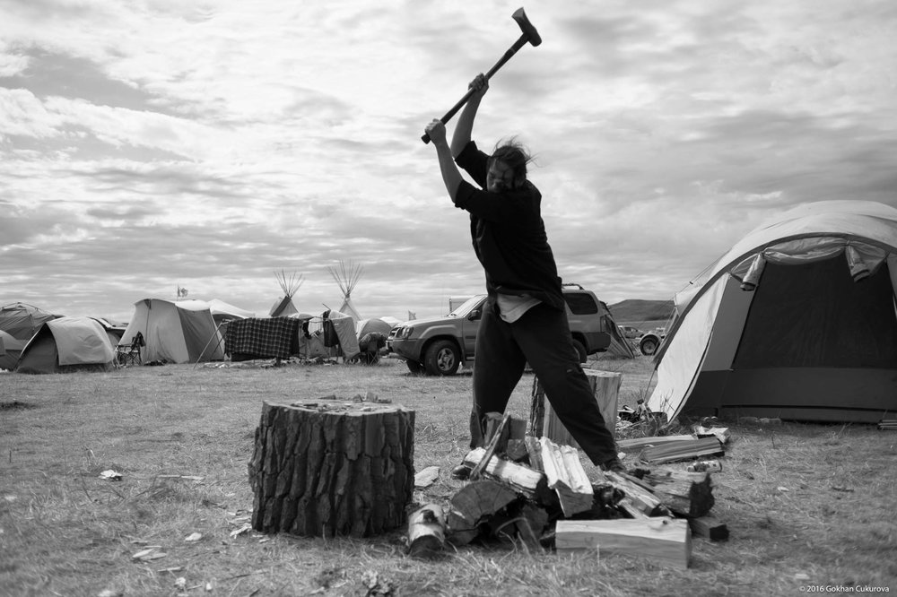 A volunteer splitting wood for Oglala Lakota kitchen
