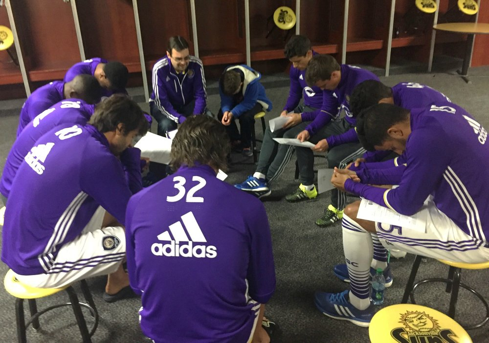 Orlando City Soccer Club chaplain Andy Searles prays with some of the MLS side's players.
