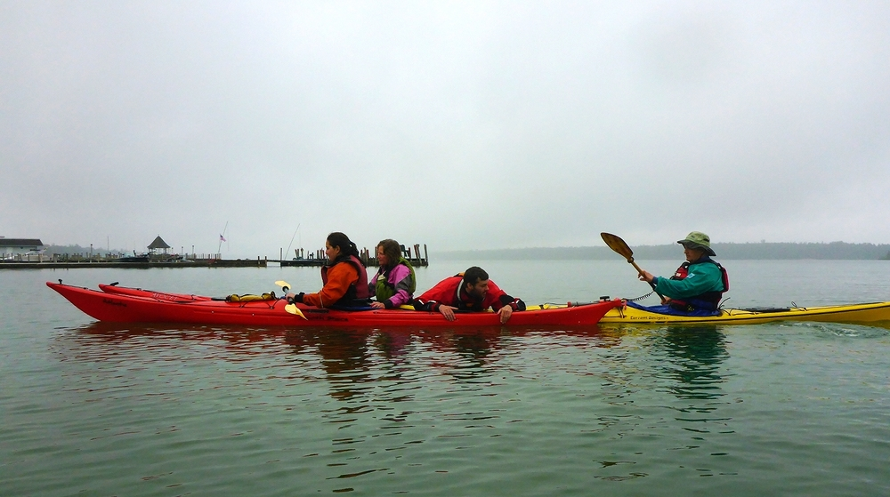 Under clouds and rain, our guides completed their 2016 training last weekend with  Sam Crawley  of  Sea Kayak Specialists .  Sam, an  ACA  Level 5 Advanced Open Water Coastal Kayaking Instructor Trainer Educator, is an excellent coach and the guides are now well prepared to instruct our guests in safe kayaking techniques.  They have also polished their skills in navigation and leading tours as well as performing rescues in several different scenarios should the situation arise.  Thank you Sam for helping us maintain the highest level of professionalism and safety on the water!
