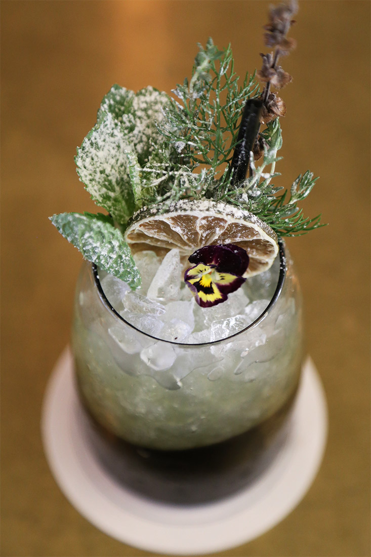 The Black and Yellow garnished with dehydrated lime, mint and rosemary sprigs and a viola.