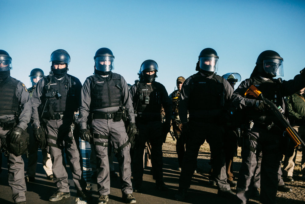 Note that police are concealing their badge numbers and faces as to avoid accountability for their actions.