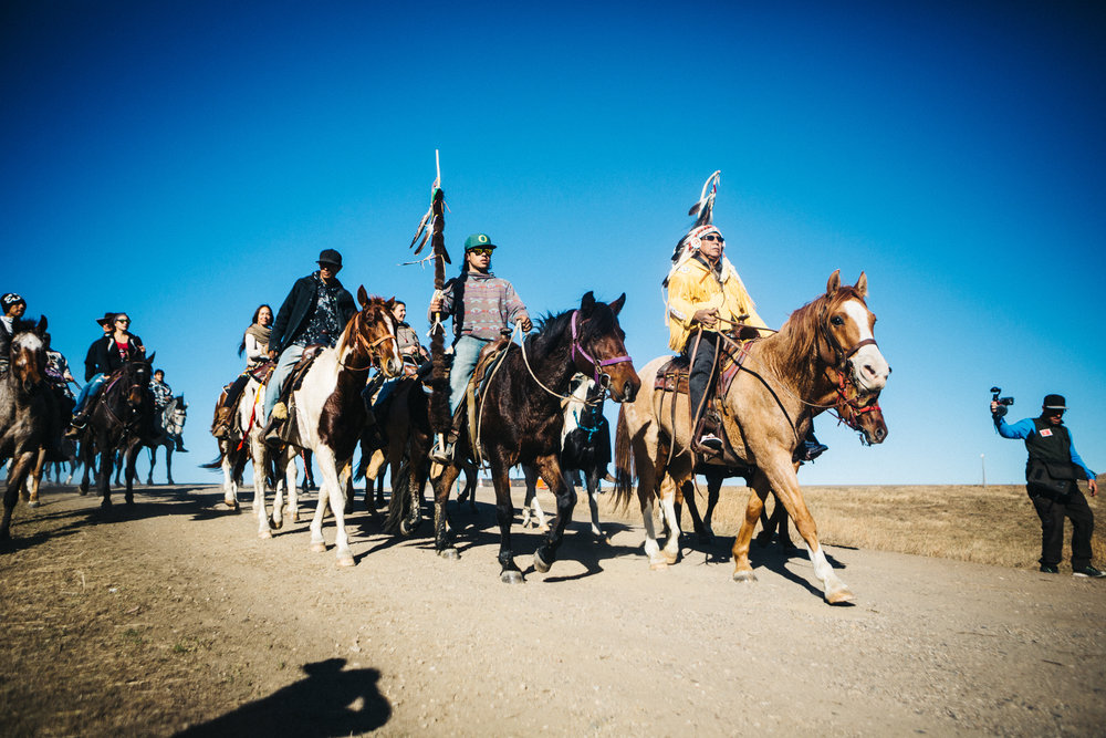 Arvol Looking Horse leads a group of Lakota riders into the Oceti Sakowa Camp for a sacred ceremony.