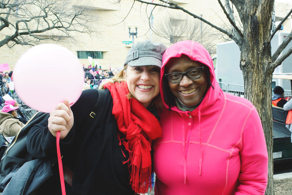 [Image description: Sarah, a blonde white woman in a red scarf, stands next to Vanessa, a black woman wearing a hot pink hoodie and glasses. The two women smile broadly with their arms around each other. Sarah holds a pink balloon.]