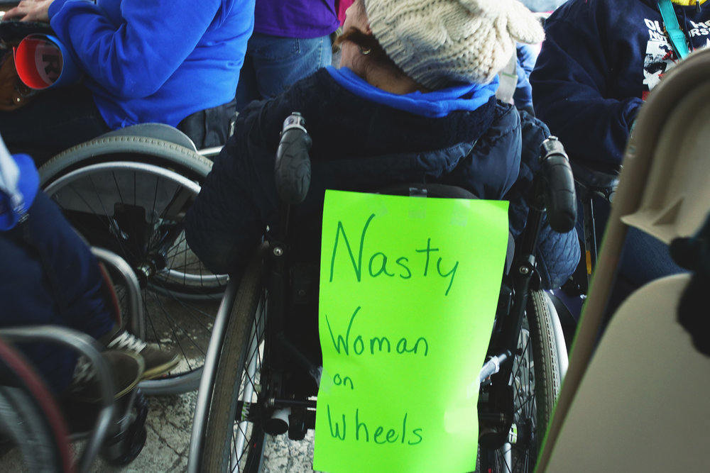 "[Image Description:  In the ADA tent a light skinned woman in a wheelchair has her back to the camera; a poster taped to the seat reads: ""Nasty woman on wheels."" She is surrounded by three other wheelchairs and a hand carries a folding chair to the right.]"