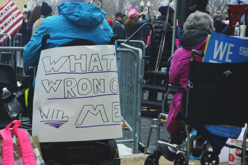 "[Image Description: Two people face away from camera towards the stage, to the left a person in a powerchair has a sign taped to their chair with the words ""What's wrong with me."" On the left, a person in a wheelchair has signs tucked between their back and the seat.]"