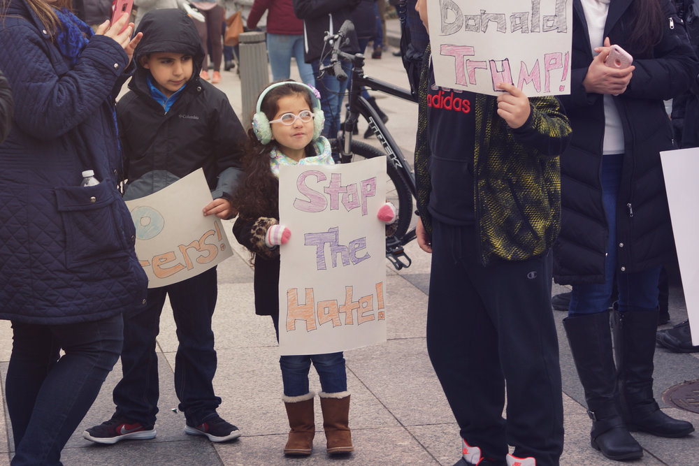 [Image Description: The photo focuses on a light skinned young girl holding a sign saying 'stop the hate!' She is wearing a dark coat is leopard print cuffs, large pastel green ear muffs and glasses. She's looking up at a boy just cropped offscreen.]