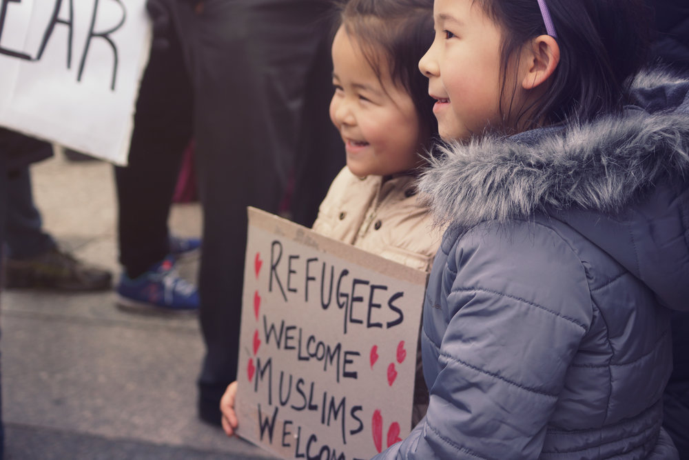 [Image Description: Two young girls of east asian descent stand together in winter coats holding a sign that reads 'refugees welcome, muslims welcome' the words are surrounded by hearts.]