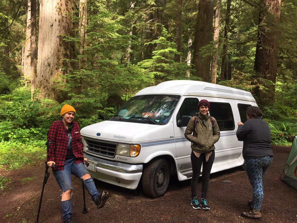 Photo Description: Eliana in a plaid shirt and a yellow hat, poses with her crutches in front of the van with two vanmates, one facing away from the camera.