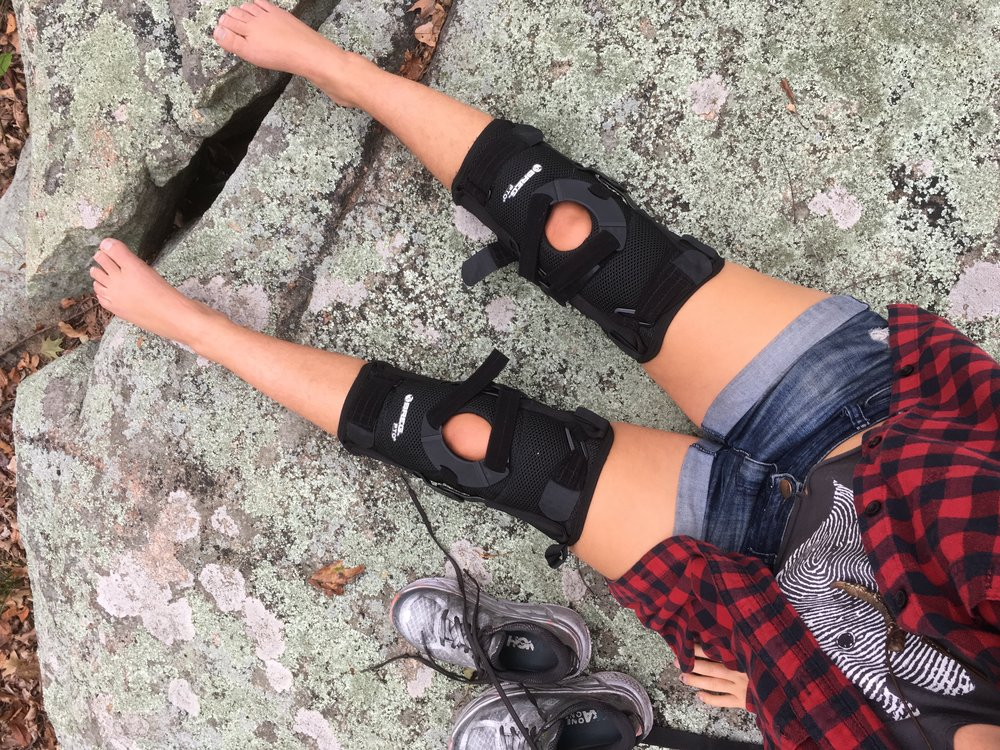 Photo Description: a shot of Eliana's legs as she lounges on a rock in a plaid shirt and shorts, her knee braces clearly visible.