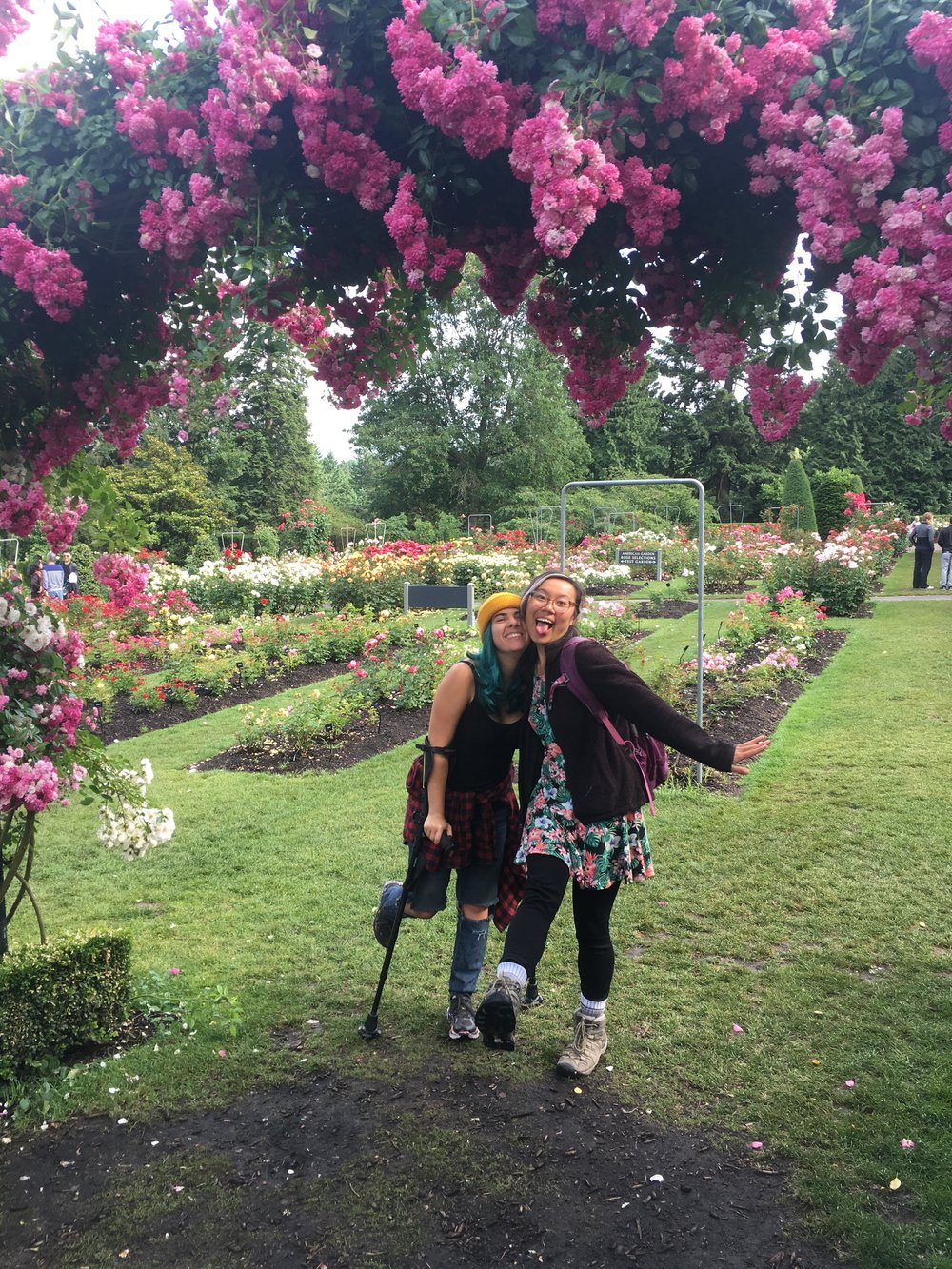 Photo Description: Eliana, still using her crutches, poses with a third vanmate in front of a flowering tree. Both women are laughing and kicking up a leg.