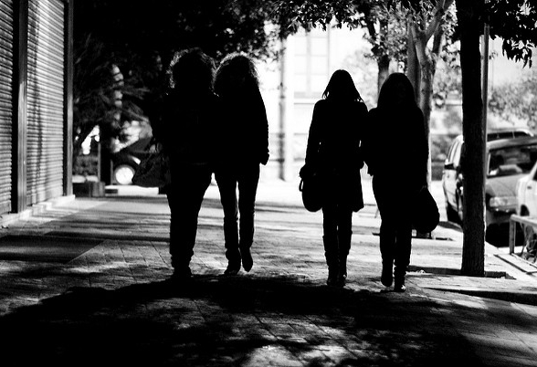 [Image description: black and white photograph of four people walking together in low light, beneath the dark shadows of tree branches.]   Andrea Donato Alemanno  / Creative Commons