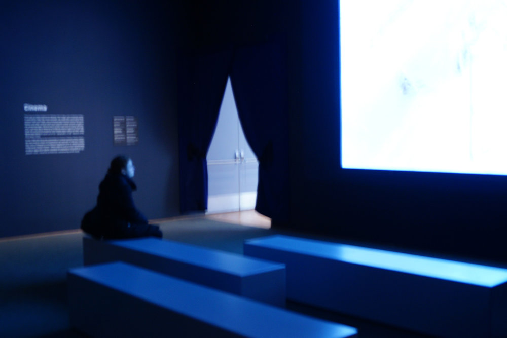 Soph Bonde/Argot Magazine. [Photo description: A woman sits slumped in a blue room, in a museum, watching an empty screen]
