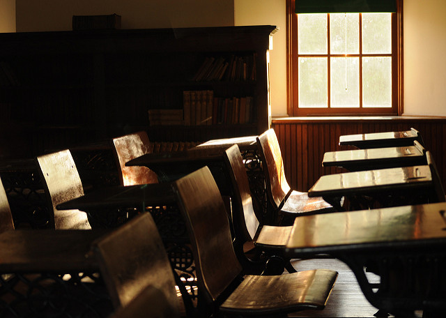 [Image description: photograph of old, wooden school desks. There is a bookshelf behind the desks, and a single bright window at the right side of the image.]   David Reber  / Creative Commons