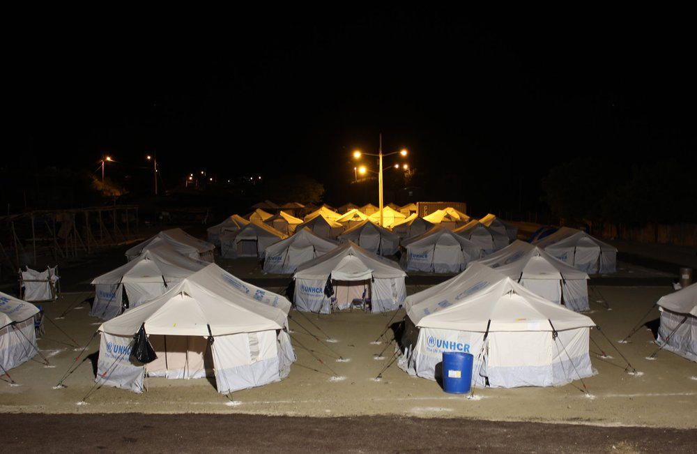 [Image description: photograph of a UN Refugee Agency camp in the small fishing town of Canoa, Manabi Province, Ecuador. It is night, and the tents are lit by harsh floodlights.]  Kimberley Brown