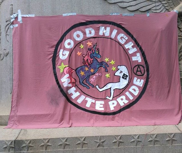 "Defend Cville  [Photo description: a red flag taped to a concrete wall says ""Goodnight White Pride"" and features a sparkly unicorn kicking a stylized KKK member. It also features an anarchist symbol, the letter ""A"" in a circle.]"