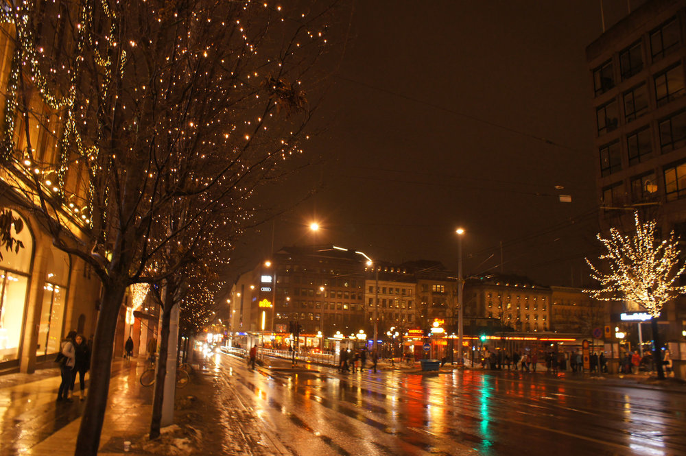 Soph Bonde/Argot Magazine. [Photo description: a wide avenue in a city at night, drenched in rain and lit by streetlights and string-lights wrapped around trees.]