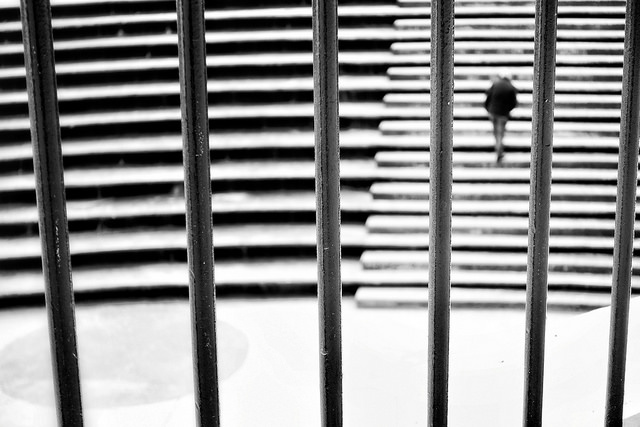 [Image description: black-and-white photograph of a wide, rounded outside staircase, with thick metal bars in the foreground of the image. On the right side of the image, a person is climbing the staircase, and their figure is blurred.]   Tuncay  / Creative Commons