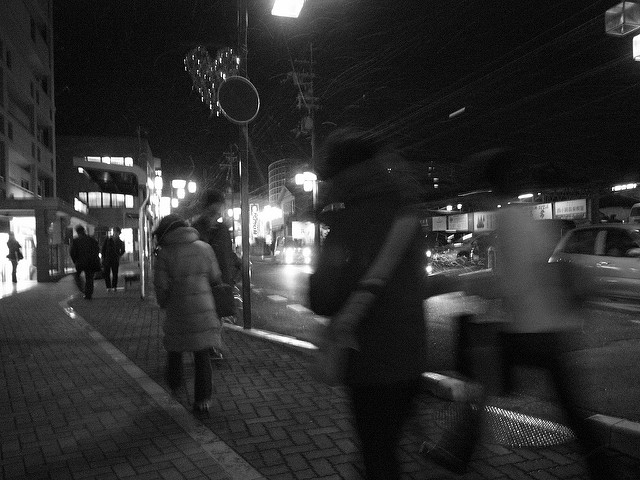 [Image description: black and white photograph of people walking down a city street at night. Their figures are blurred.] Toshiyuki IMAI / Creative Commons