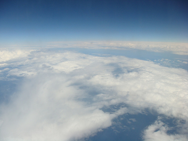 [Image description: aerial photograph of blankets of thick, white cloud between twin blue planes of sky and earth.]  souz gerbino / Creative Commons