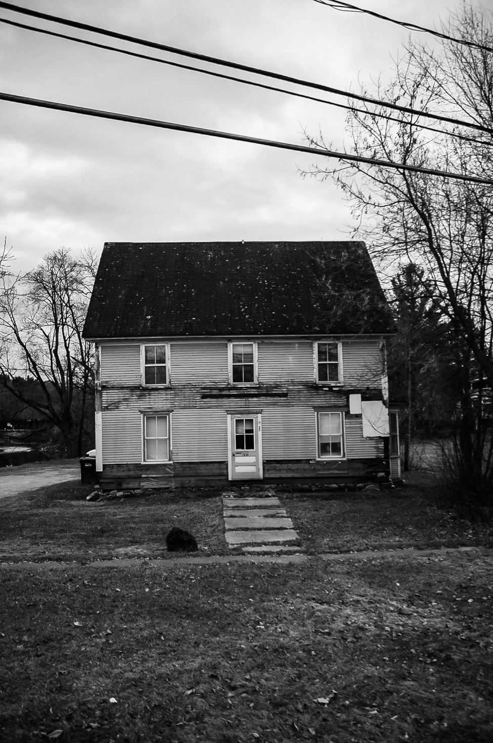 [Image description: black and white photograph of an old wooden house. There is a dark crack running horizontally across the front of the house, and a worn stone pathway leading up to the front door.]  Nanette Thiam
