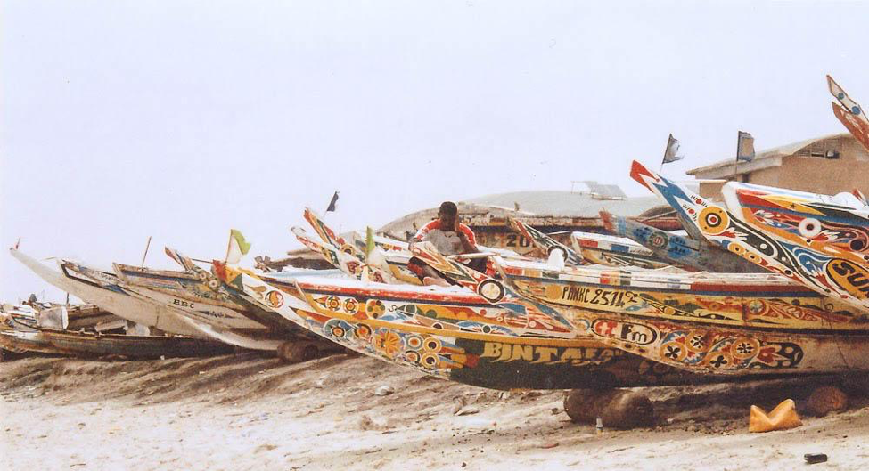 [Image description: photograph of brightly and intricately decorated boats lined up in a dock on on a beach. A person is bending over one of the boats in the centre of the image.]  Nanette Thiam