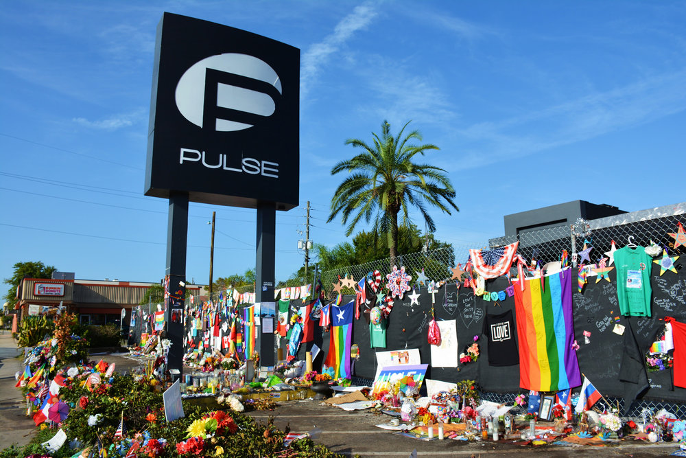 Photo Credit: Walter Pro   [Image Description: a memorial with flowers, rainbow flags, and candles set up in front of Pulse Nightclub after the Orlando shooting June 2016]
