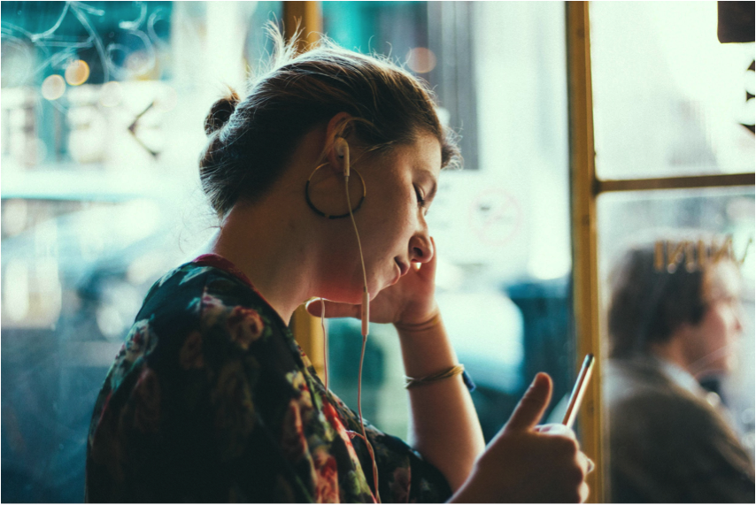 Photo Credit: Siddarth Bhogra   [Image Description: Colorful photograph of a feminine person standing by a window, with earphones in her ears while she listens to something on her phone]