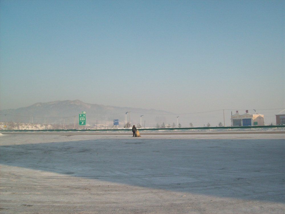 [Image description: photograph of a wide expanse of paved ground, lightly covered with scraped ice. There is a single, small figure of a person in the very middle of the picture, and there are highway signs behind them. The sky is clear, and a large, rocky mountain is visible in the background of the image.] Naomi Porter-Lupu