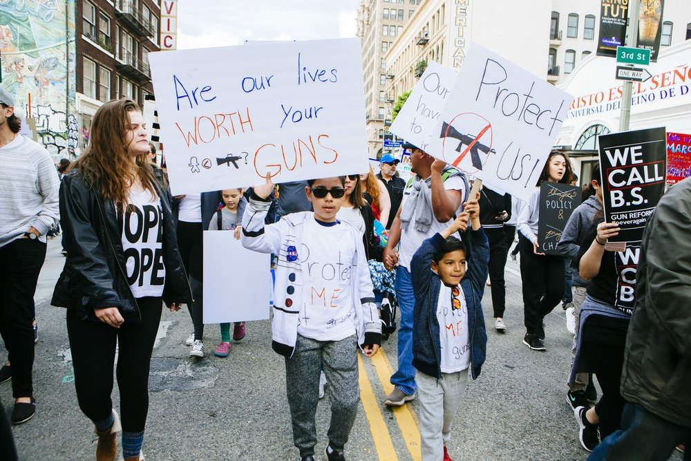 "[Image Description: Two children hold signs in the center of a street. Their signs say ""Are our lives worth your guns?"" And ""Protect Us!"" with a crossed out drawing of a gun."