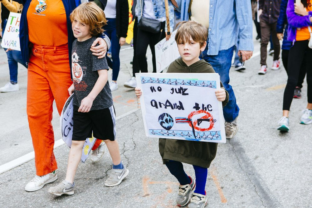 [Image Description: Two young children march in the street holding signs, one holds their sign next to his body, the other holds a sign that is written in childish handwriting and I honestly can't read it, it has a drawing of a globe, a backwards American flag and a crossed out gun.]