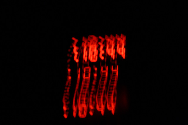 [Image description: photograph of an alarm clock display. The background is black, and the red numbers are blurred as if smeared or melted.]  csunday / Creative Commons