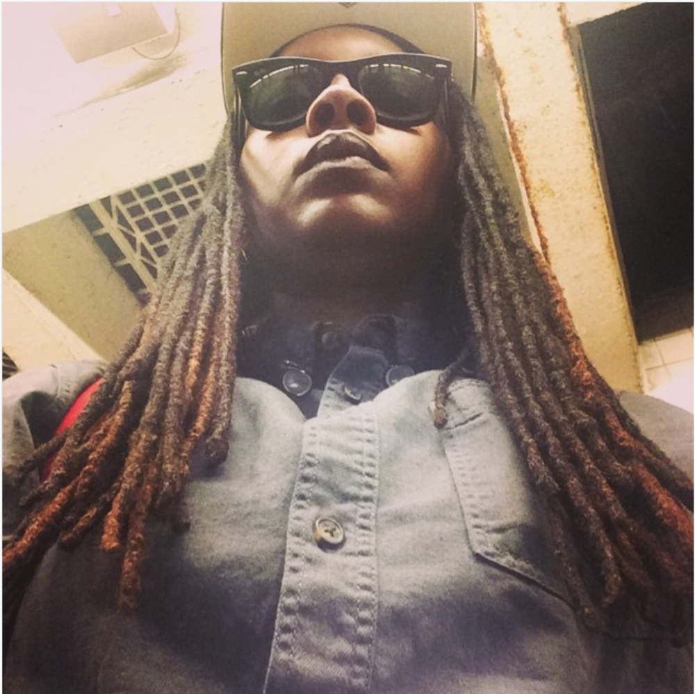 [Image description: photograph taken from below of a person wearing a blue-grey button up shirt. The person has long locs, and is wearing sunglasses and a hat.]  Photo credit danieonthemove