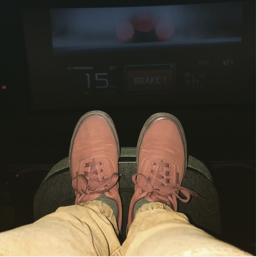 [Image description: photograph of a pair of feet, soles flat against the back of a chair. The shoes are reddish-brown sneakers. The hem of a pair of tan pants is also visible.]  Photo credit danieonthemove