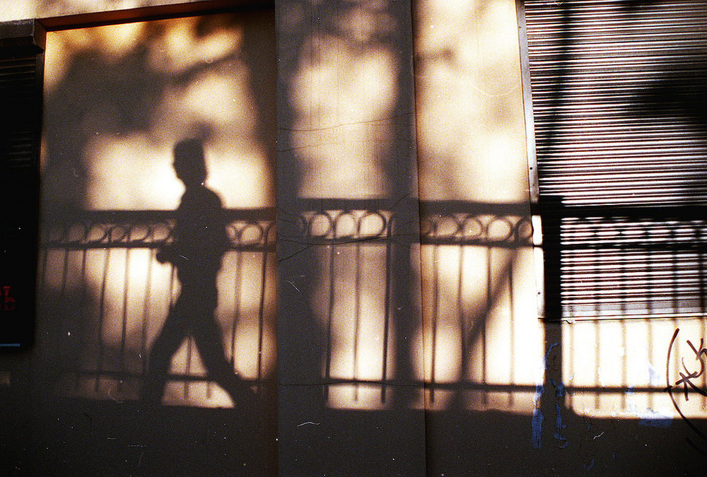 Photo by  Zaytsev Artem  via  Flickr , creative commons.  [Image description: The shadow of a person is seen against a wall. The person is walking past a fence.]