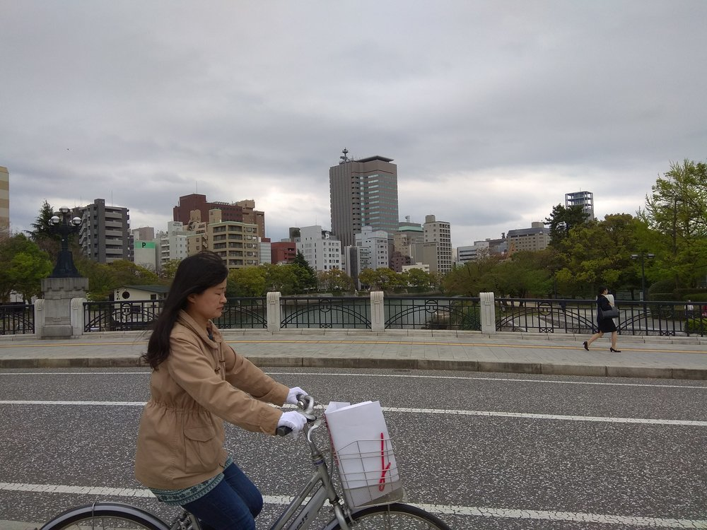 [Image description: photograph of a city bridge. High-rise buildings are visible in the background, and a person with long, dark hair is riding a bicycle in the foreground, crossing the bridge from left to right.]