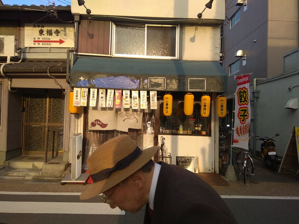 [Image description: photograph of the front of a small dumpling restaurant. There are numerous price signs hanging from the awning. A person wearing glasses and a straw hat is in profile in the foreground.]