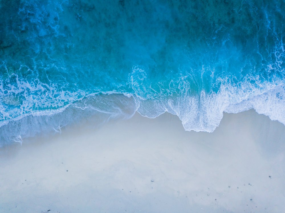 Photo by  Nattu Adnan  on  Unsplash    [Image Description: an aerial photograph of crisp blue waves washing upon a white sand shore]