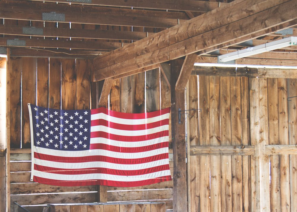 Photo by  Michael Browning  on  Unsplash    [Image Description: The flag of the United States of America hangs off-center inside a wooden room with ceiling rafters, illuminated by ambient light.]