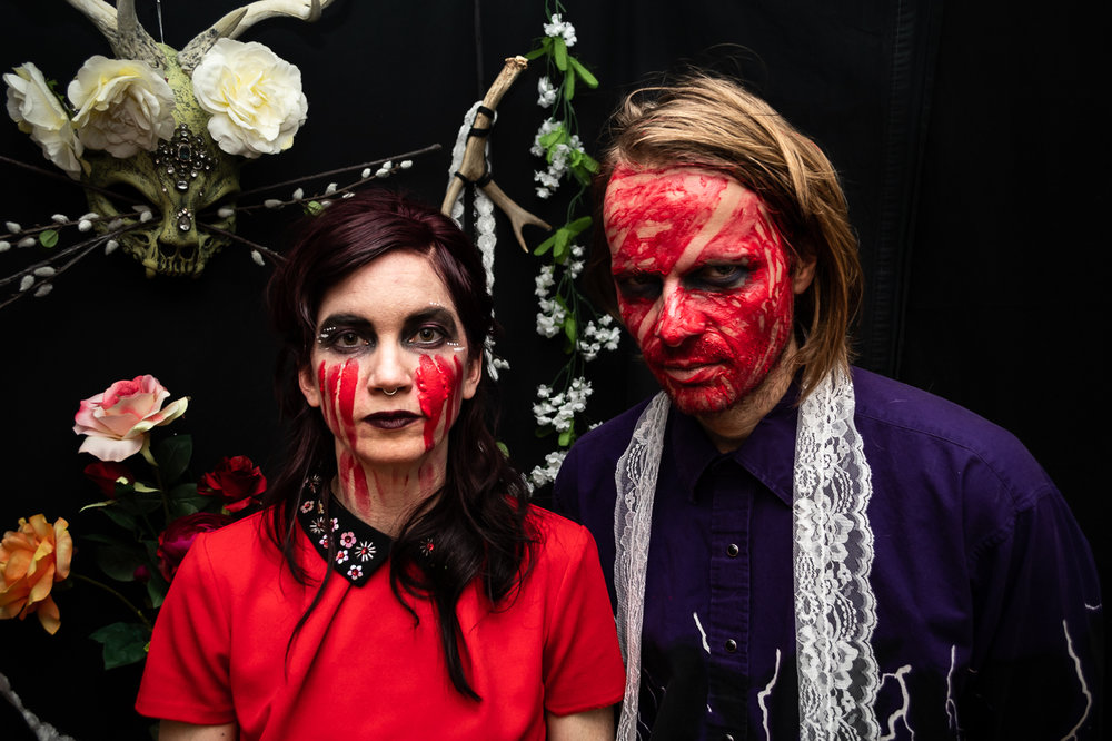 Photo by  churchfire     [Image Description: Two people stand side by side in front of a background of flowers, skulls, and antlers. A red substance resembling blood streak their faces.]
